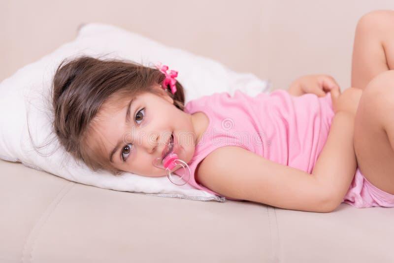 躺在与安慰者的床上的逗人喜爱的女孩画象 免版税图库摄影
