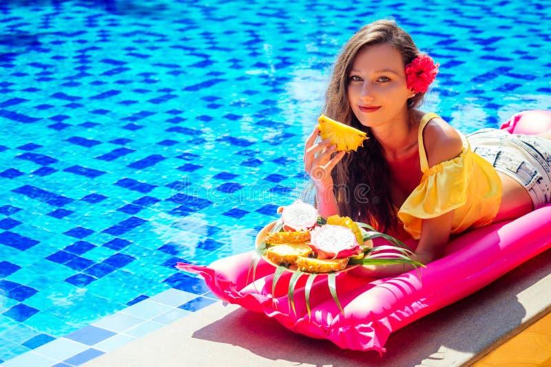 躺在充气粉色床垫上的美丽女孩,吃热带水果芒果、龙果、木瓜和菠萝 免版税库存照片