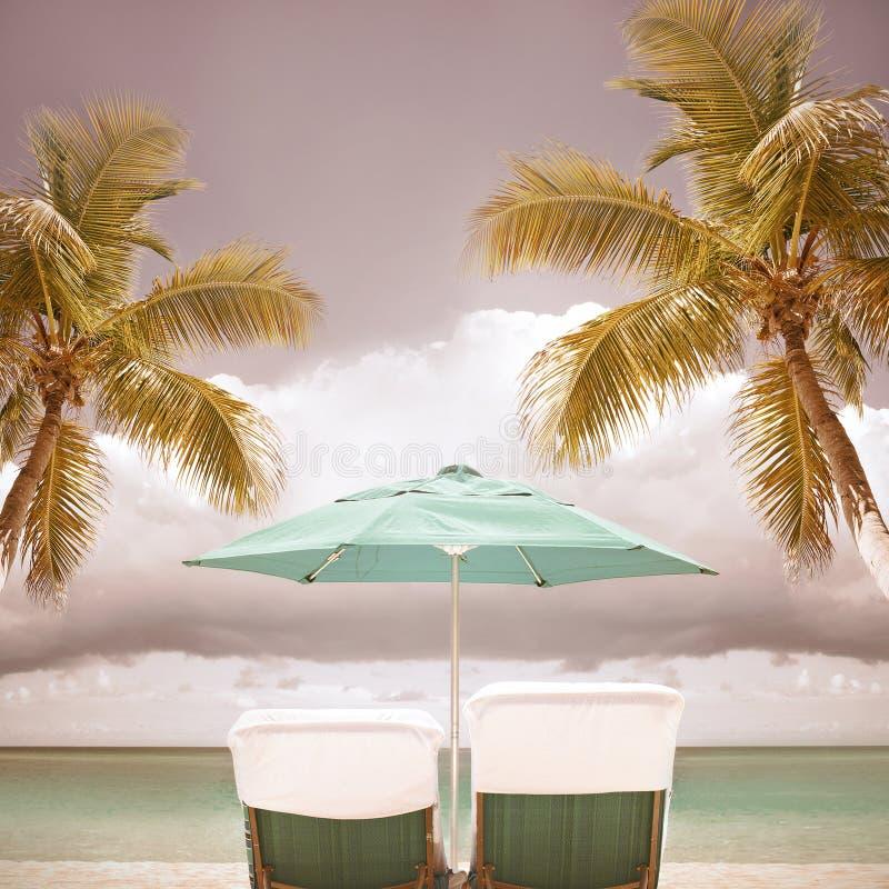 躺椅和伞在一个热带天堂靠岸 免版税库存照片