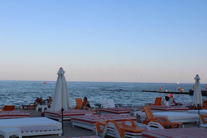 躺椅和阳伞在海滩 免版税图库摄影