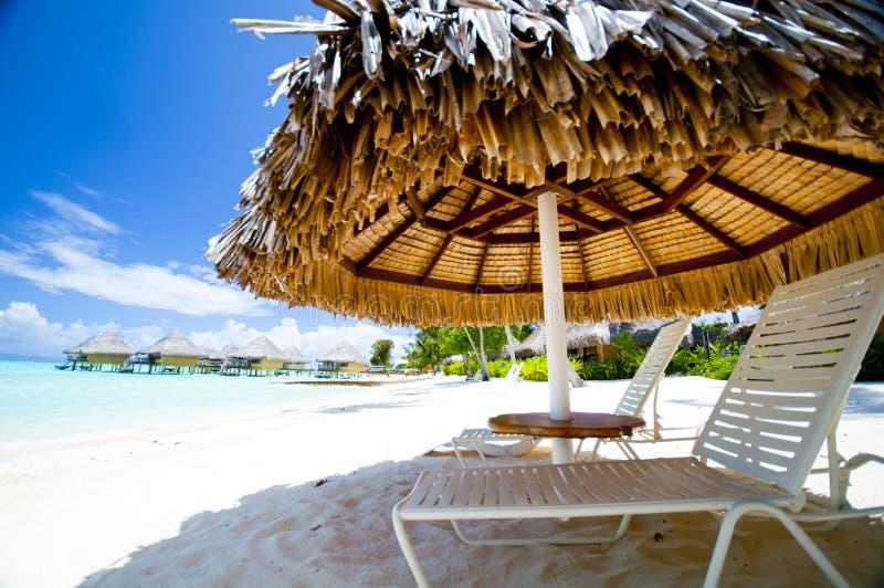 躺椅在海滩的伞下 免版税库存照片