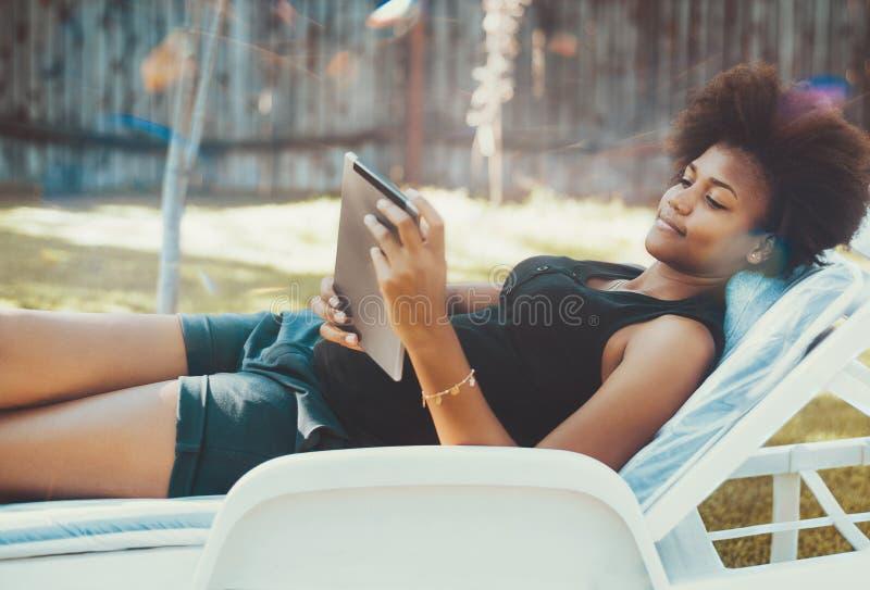 躺椅的蓬松卷发女孩有数字式片剂的 免版税库存照片