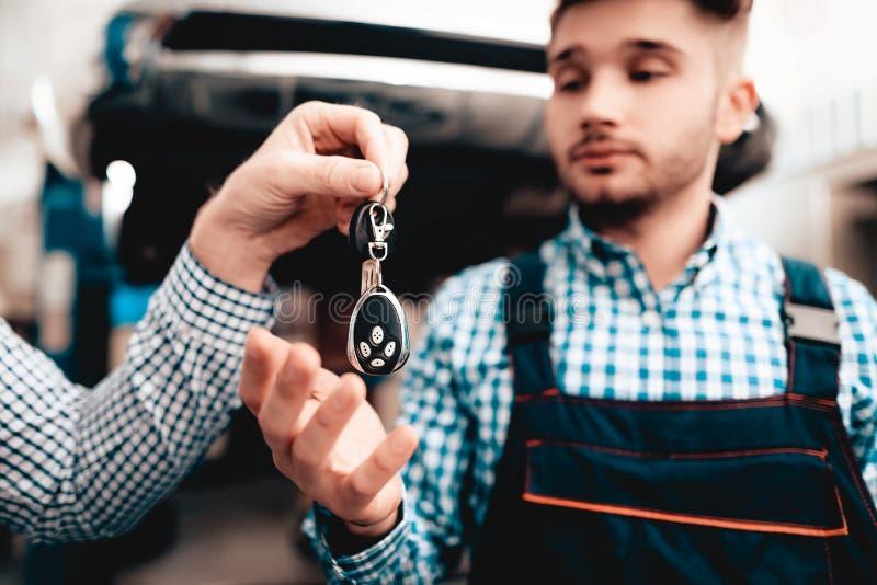 车主给钥匙车库的技工 免版税库存照片