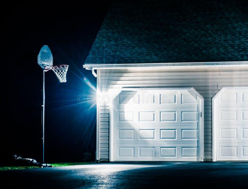 车库和篮球篮在晚上 库存照片