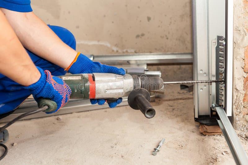 车库门设施 工作者操练螺栓的一个孔 免版税库存照片