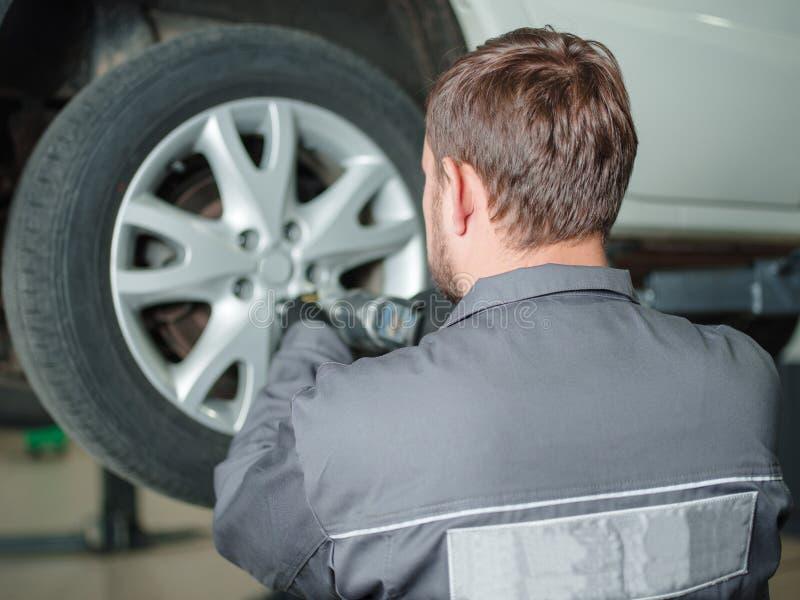 车技工更换白色汽车的轮子 户内 免版税库存照片