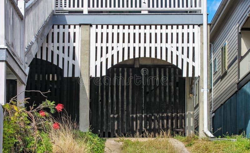 车棚车库特写镜头在一个Queenslander房子下的有在曲拱和分开的车道的白板的 库存照片