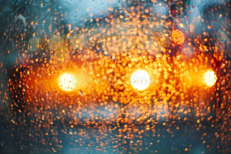 车灯通过与雨下落的玻璃 免版税库存图片