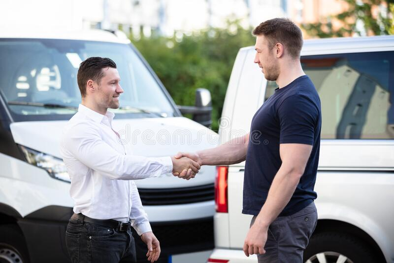 车祸后汽车受损,面带微笑的男子握手 免版税库存照片