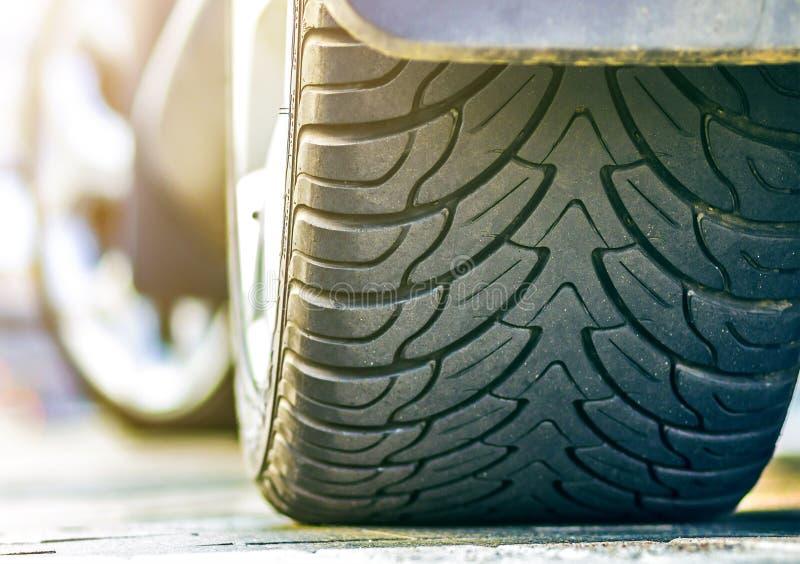 车轮和在轻的被弄脏的户外背景的黑橡胶轮胎保护者特写镜头细节有铝圆盘的 耐久性, 免版税库存照片