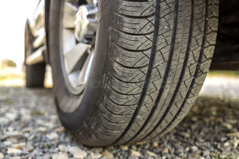 车轮和在轻的被弄脏的户外背景的黑橡胶轮胎保护者特写镜头细节有铝圆盘的 库存图片