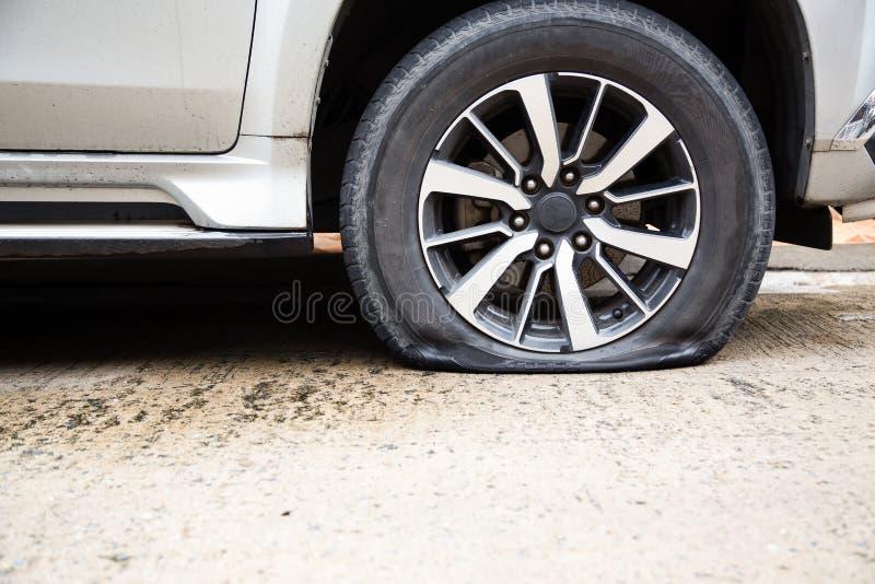 车轮泄了气的轮胎特写镜头在路,车胎泄漏由于捣在街道等待的修理的钉子或改变的 图库摄影