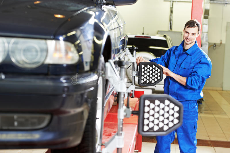 车轮调整的汽车修理师与计算机 库存图片