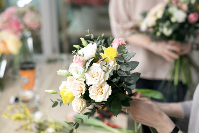 车间卖花人,做花束和花的布置 收集花的花束妇女 软绵绵地集中 图库摄影