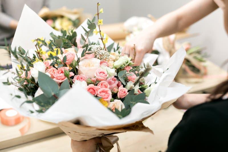 车间卖花人,做花束和花的布置 收集花的花束妇女 软绵绵地集中 免版税图库摄影