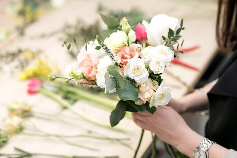 车间卖花人,做花束和花的布置 收集花的花束妇女 软绵绵地集中 免版税库存照片