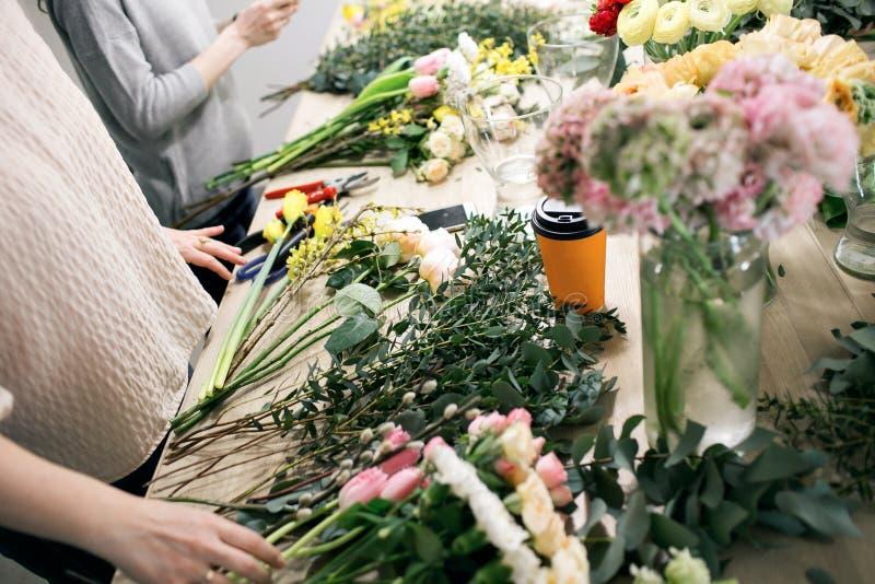 车间卖花人,做花束和花的布置 收集花的花束妇女 软绵绵地集中 免版税库存图片
