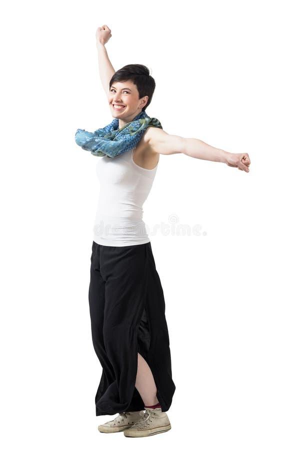 转动与被举的胳膊的快乐的激动的妇女穿宽裤子和围巾 库存照片
