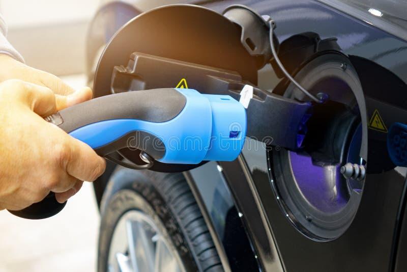 转动充电汽车的人 EV汽车或电车在充电站 库存图片
