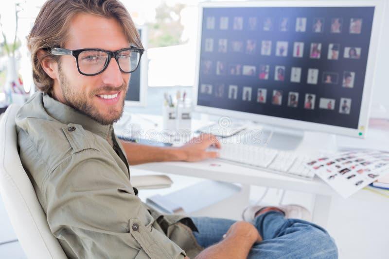 转动和微笑对他的书桌的照片编辑程序 免版税库存图片