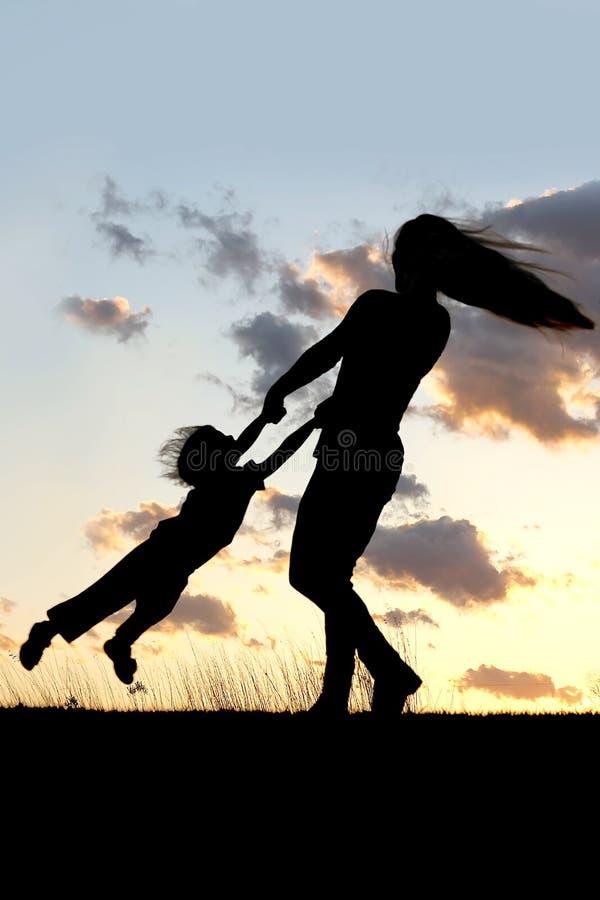 转动和跳舞与孩子的母亲剪影在日落 免版税库存图片