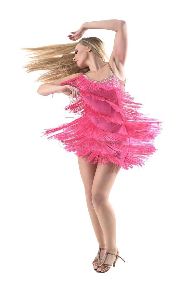 转动和跳舞与流动的头发的白肤金发的拉丁美州的舞蹈家侧视图看  免版税图库摄影