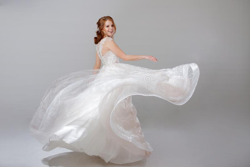 转动在一套弯曲的婚礼礼服的少妇 豪华婚礼礼服的妇女新娘 轻的背景 免版税库存照片