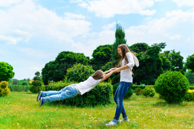 转动在夏天公园的女孩和男孩 库存照片