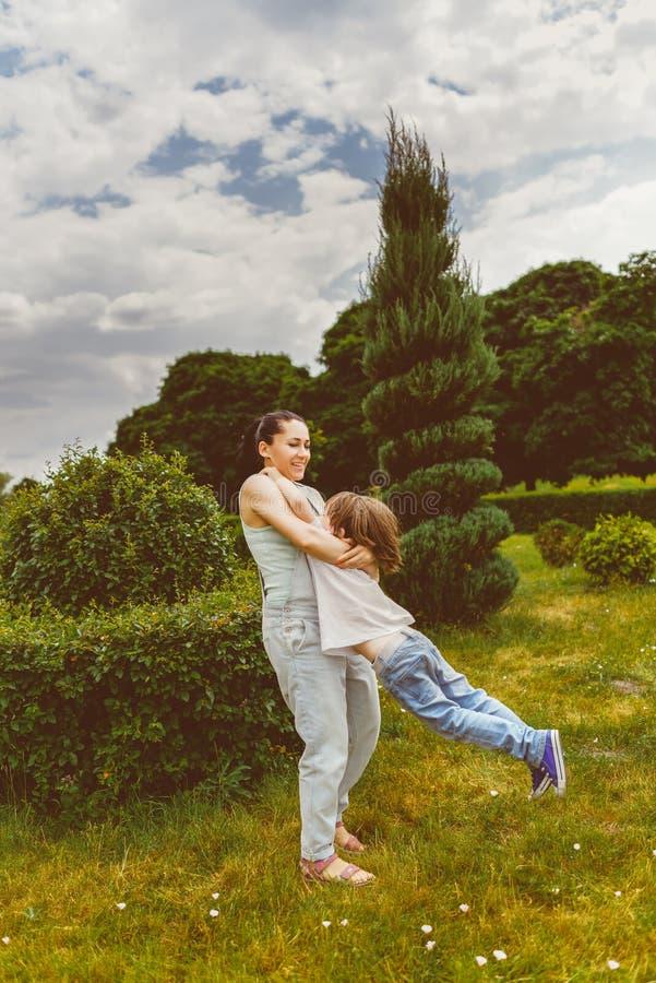 转动在夏天公园的母亲和儿子 柔和曲调 库存图片