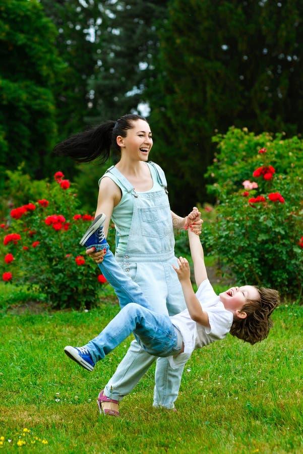 转动在夏天公园的母亲和儿子 免版税库存图片