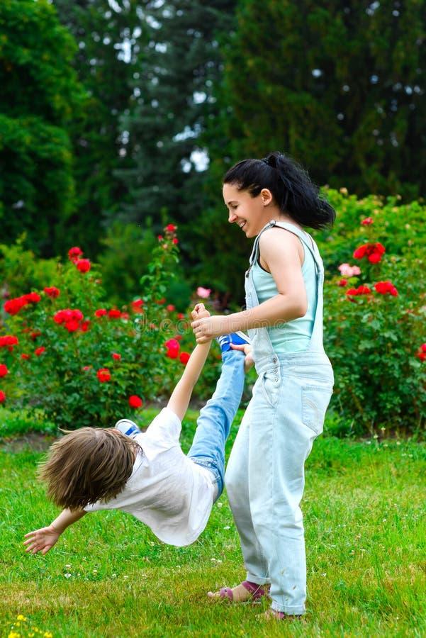 转动在夏天公园的母亲和儿子 免版税图库摄影