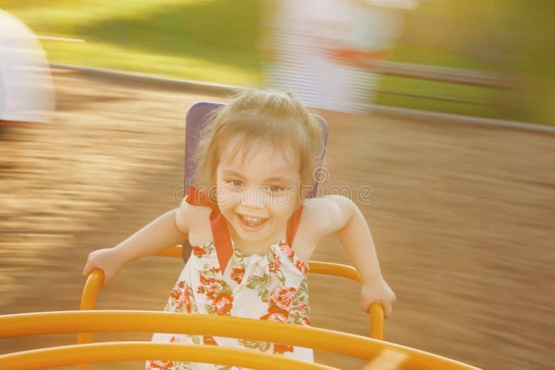 转动在操场中的儿童` s转盘的小女孩 免版税库存照片