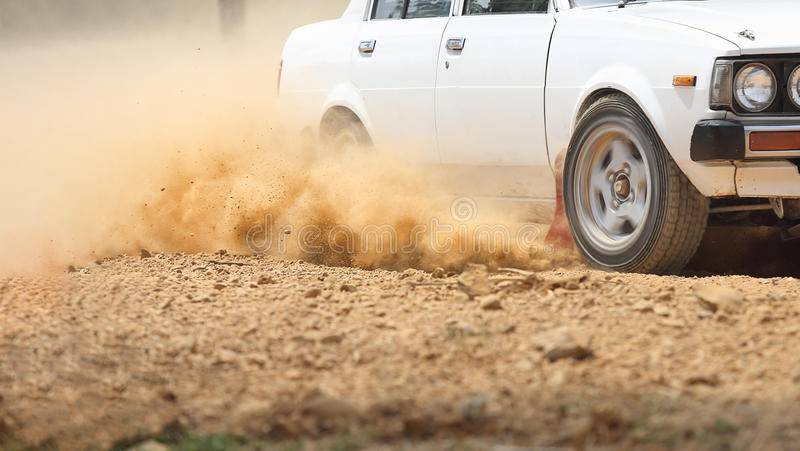 转动在泥铺跑道的减速火箭的集会汽车 免版税库存图片