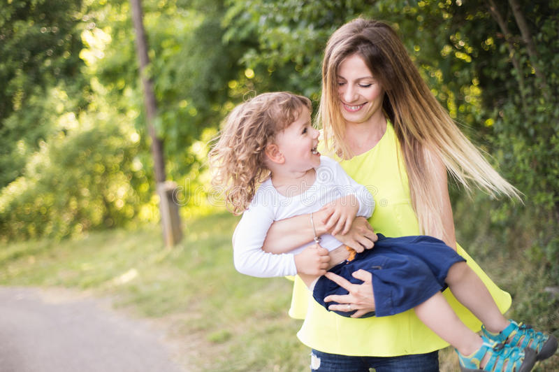 转动她的儿子的美丽的母亲 晴朗的夏天本质 免版税库存图片