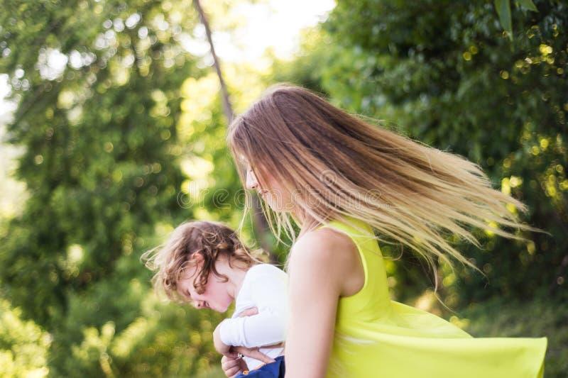 转动她的儿子的美丽的母亲 晴朗的夏天本质 库存照片