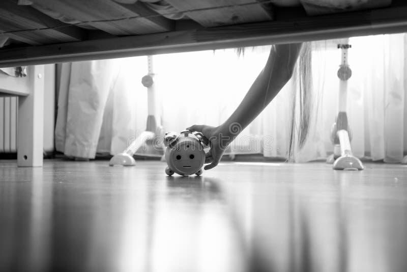 转动敲响的闹钟的女性手的特写镜头黑白图象在床下 图库摄影