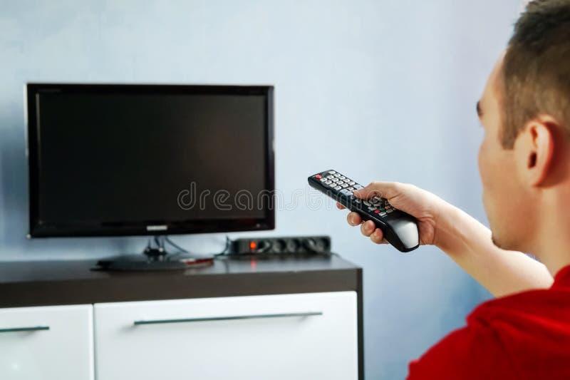 转动电视开关 有遥控的人,电视的前面 年轻人交换在遥控的渠道从 库存图片