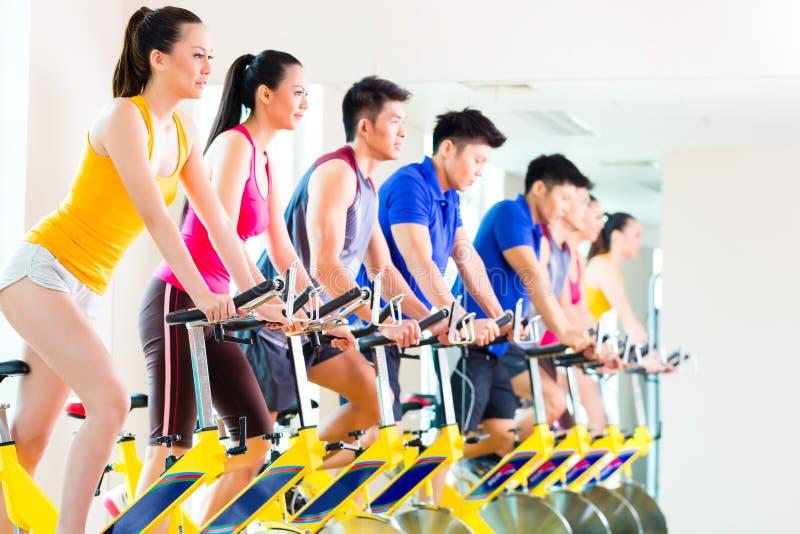 转动的自行车训练的亚裔人民在健身健身房 免版税库存照片