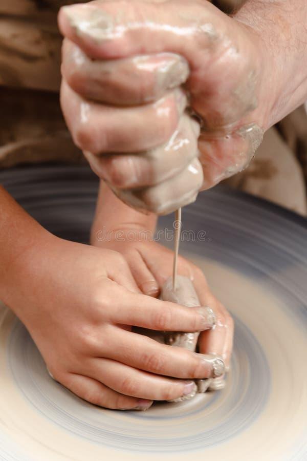 转动的陶瓷工` s转动和对从上面被采取的此的黏土商品 雕刻他的有黏土杯子的手在横式转盘 交上 免版税库存图片