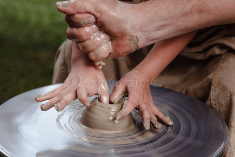 转动的陶瓷工` s转动和对从上面被采取的此的黏土商品 雕刻他的有黏土杯子的手在横式转盘 交上 免版税图库摄影