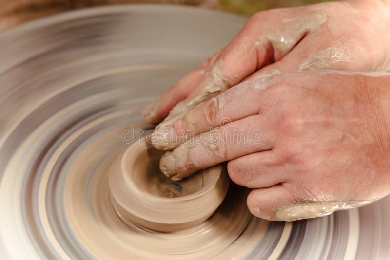 转动的陶瓷工` s转动和对从上面被采取的此的黏土商品 雕刻他的有黏土杯子的手在横式转盘 交上 免版税库存照片