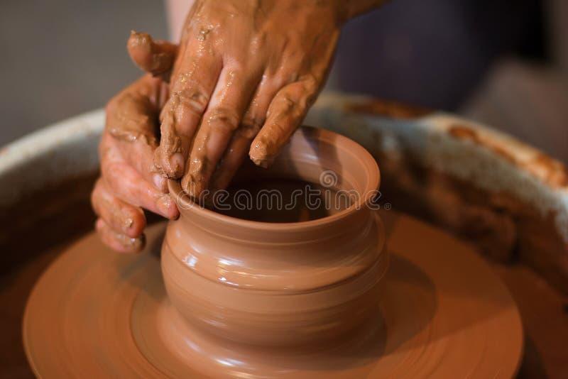 转动的陶瓷工` s转动和对从上面被采取的此的黏土商品 雕刻他的有黏土杯子的手在横式转盘 库存图片