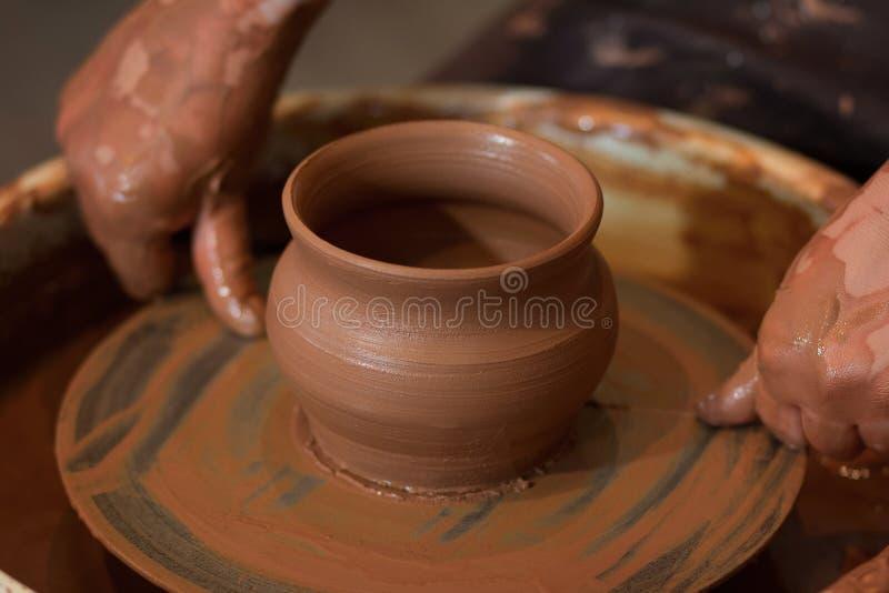 转动的陶瓷工` s转动和对从上面被采取的此的黏土商品 雕刻他的有黏土杯子的手在横式转盘 免版税库存照片