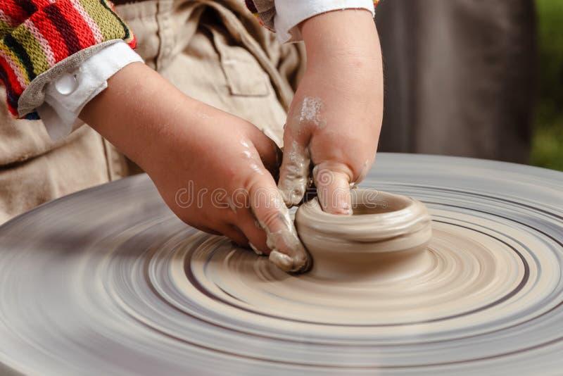 转动的陶瓷工` s转动和对从上面被采取的此的黏土商品 雕刻他的有黏土杯子的手在横式转盘 库存照片