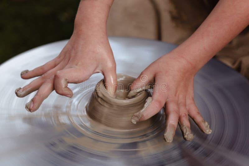 转动的陶瓷工` s转动和对从上面被采取的此的黏土商品 雕刻他的有黏土杯子的手在横式转盘 免版税库存图片