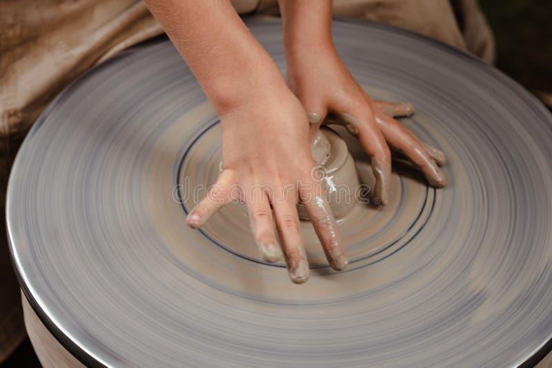 转动的陶瓷工` s转动和对从上面被采取的此的黏土商品 雕刻他的有黏土杯子的手在横式转盘 免版税图库摄影