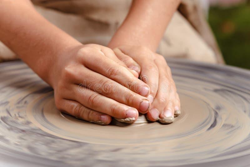 转动的陶瓷工` s转动和对从上面被采取的此的黏土商品 雕刻他的有黏土杯子的手在横式转盘 图库摄影
