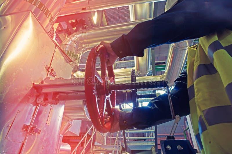 转动红色轮子阀门的工业工厂劳工 库存图片