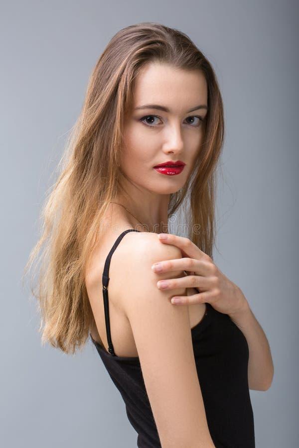 转动美丽的金发碧眼的女人,看在她的肩膀 库存图片