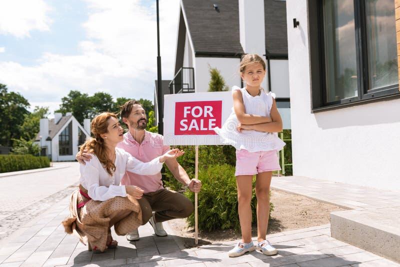 转动远离她的父母的不快乐的女孩 免版税库存图片